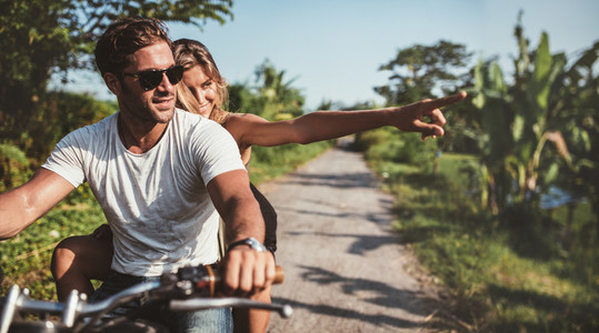 Beautiful young couple riding motorbike