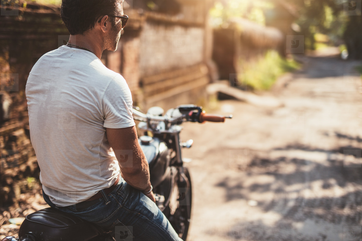 Young man sitting on his motorcycle