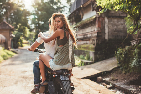 Attractive young woman on bike with her boyfriend
