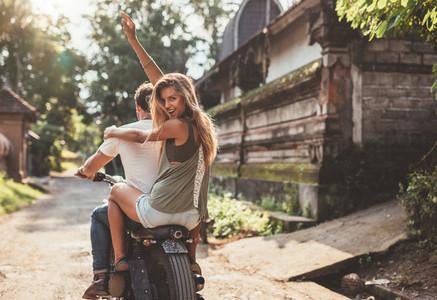 Couple enjoying motorcycle ride on village road