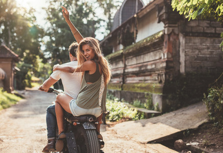 Couple enjoying motorcycle ride on village road