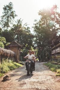 Couple enjoying motorcycle ride through a village road