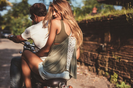 Attractive female with her boyfriend on motorcycle