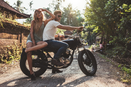 Couple hanging out in countryside with motorcycle
