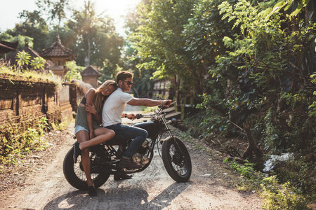 Young man and woman on motorbike in a village