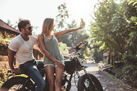 Young couple taking selfie on motorcycle