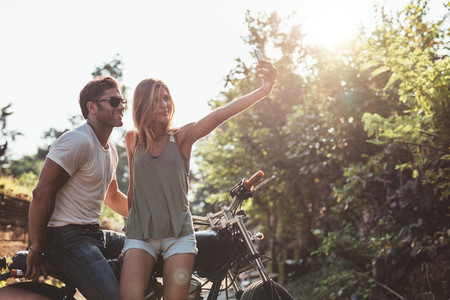 Couple taking a selfie on road trip with motorcycle