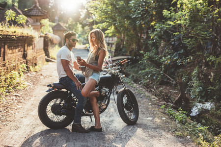 Cheerful young couple with motorcycle on country road