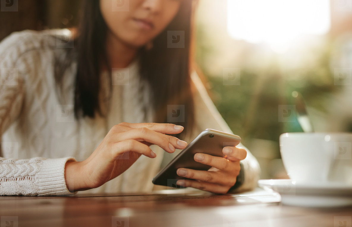 Woman sitting at a table using mobile phone
