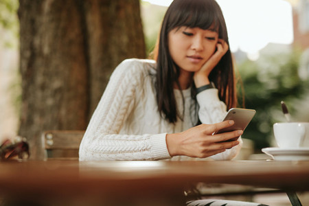 Chinese woman  with mobile phone at outdoor cafe