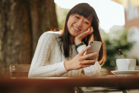 Smiling woman using smartphone in cafe