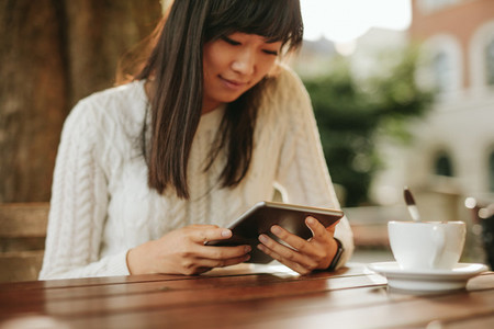 Chinese woman using digital tablet at outdoor cafe