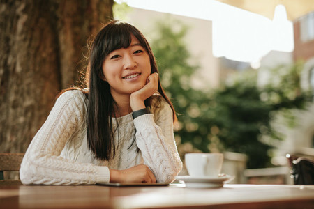 Attractive girl sitting at outdoor cafe and smiling