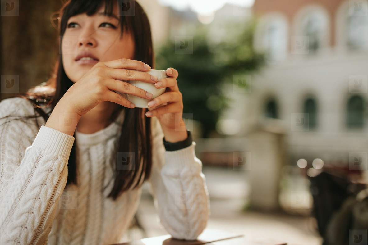 Chinese woman at outdoor cafe with cup of coffee