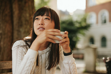Beautiful young chinese woman having coffee at cafe