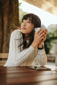 Chinese woman having coffee at outdoor cafe