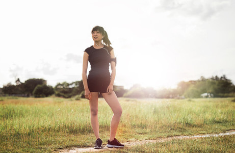 Female runner standing outdoors in morning