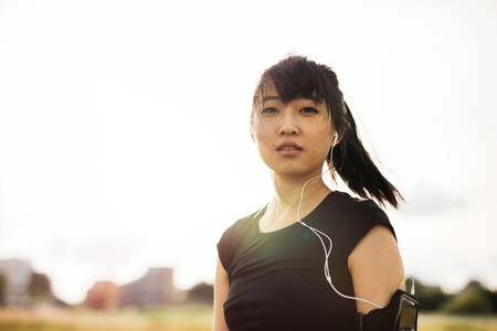 Young woman relaxing and listening music after running early mor