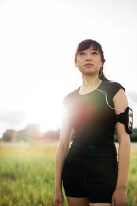 Chinese woman in sportswear standing outdoors in city park