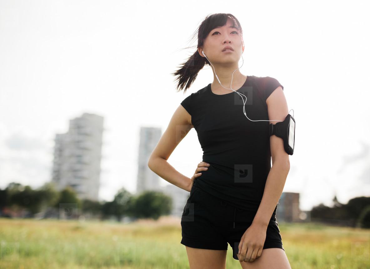 Female runner standing in urban park