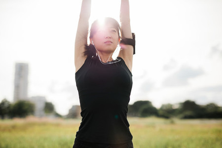 Fitness female stretching hands at park