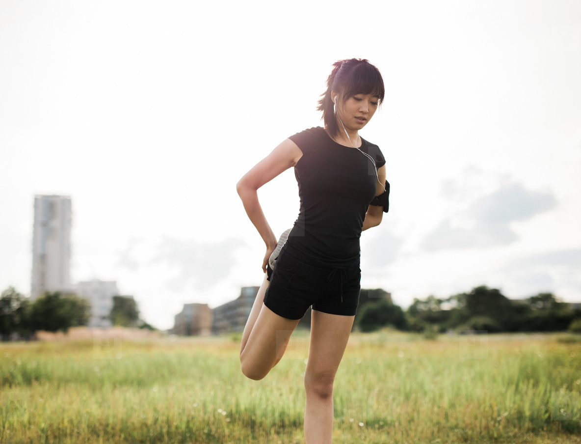 Fit woman stretching her legs at urban park