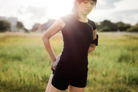 Female in sportswear doing warm up exercise in morning at park