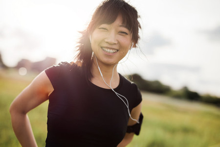 Happy female running standing outdoors and smiling