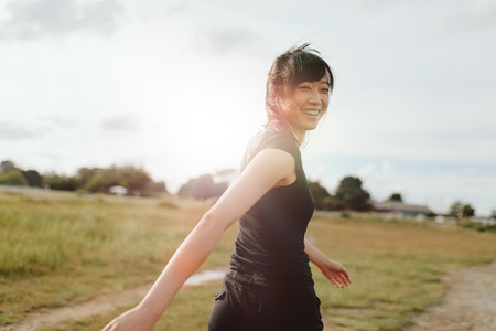 Woman runner walking on field in morning