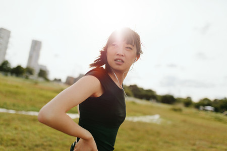 Fitness female on field glancing back