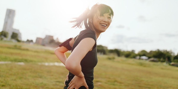 Female runner laughing on field in morning