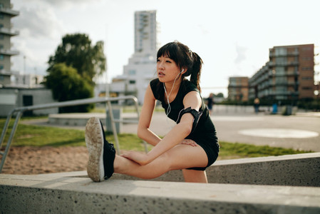 Young woman stretching in sports gear