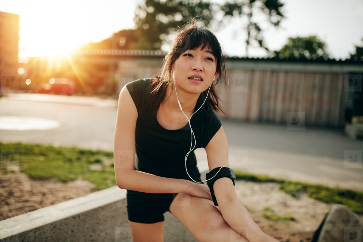 Female runner stretching legs before running workout