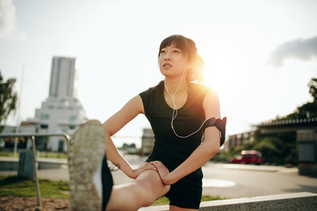 Sporty woman stretching her leg in park