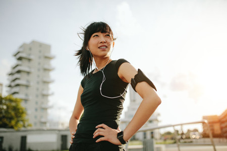 Asian female taking a break during morning run