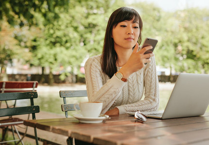 Attractive woman using smartphone at coffee shop