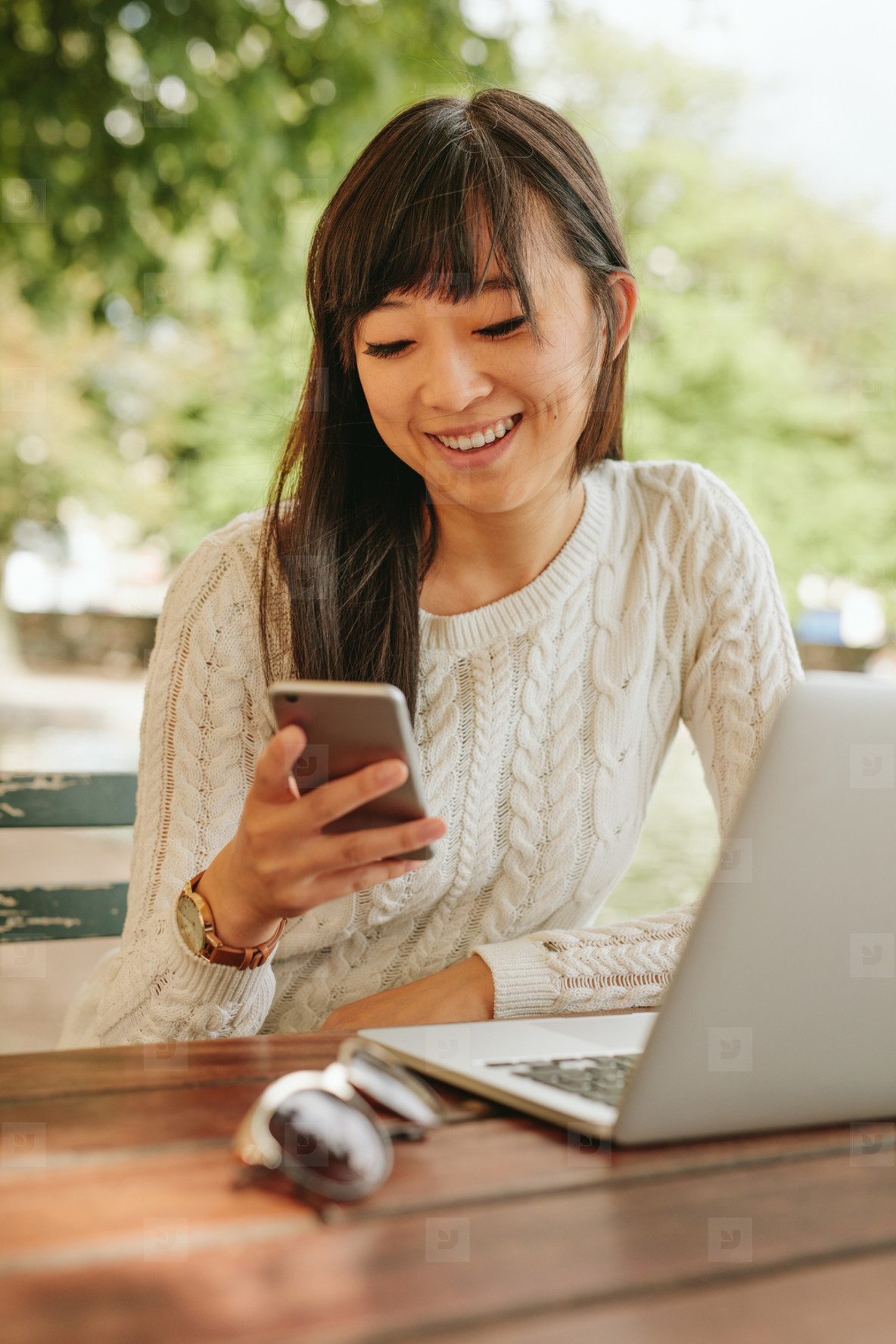 Smiling woman using cellphone at coffee shop