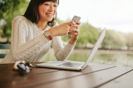 Woman using cell phone at cafe
