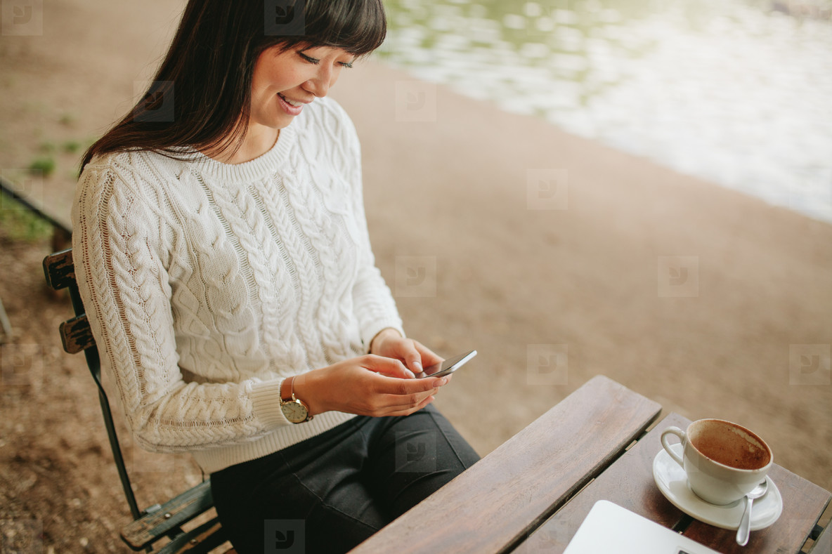 Woman sitting at cafe using mobile phone and smiling