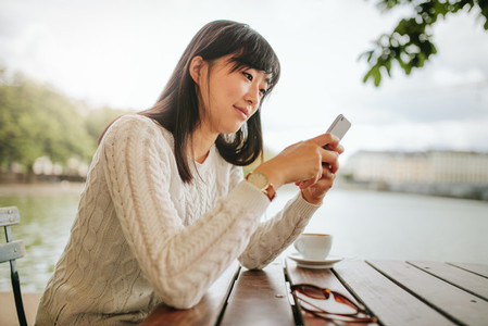 Beautiful asian woman using mobile phone at cafe