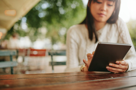 Woman using tablet at coffee shop
