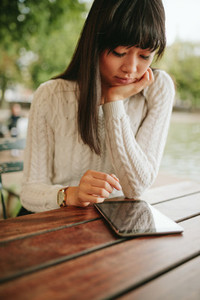 Young woman using digital tablet at outdoor cafe