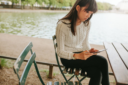 Woman at cafe by the pond using digital tablet