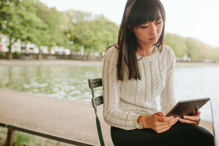 Young woman sitting at cafe with digital tablet