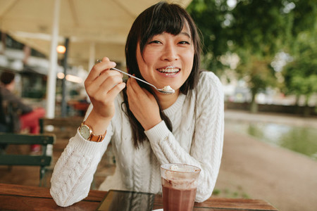 Chinese female enjoying dessert at cafe