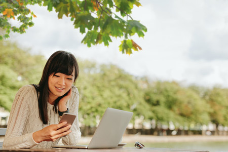 Smiling young woman using mobile phone at outdoor cafe