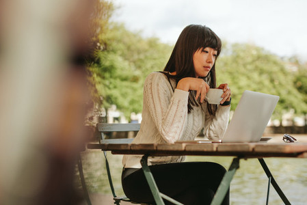 Female having coffee at cafe and using laptop