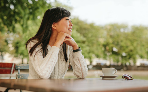 Asian woman spending free time at outdoor cafe
