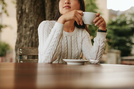 Young woman holding a cup of coffee at cafe