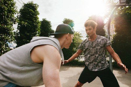Two teenage friends playing basketball